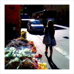 Emma walking past a flower stand on her way to Ressu School.