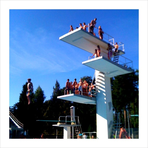 A young kid jumping off the 10 meter platform at the Stadium Swimming Pool.