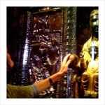 Anita touches the Black Virgin at Montserrat.