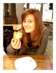 Emma with a cute smile and a cinnamon croissant.