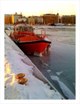 A pilot boat in Helsinki harbor looks to be locked in ice.