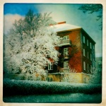 A beautiful building behind a tree covered in snow.