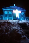 A cross is illuminated in front of Helsinki Cathedral.