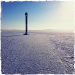 A channel marker used for navigation in the Helsinki harbor is frozen in the ice.