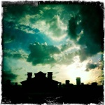 Evening clouds with silhouettes of the tops of the surrounding apartment buildings.