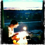 Kim doing needlepoint with the sunset in the background.