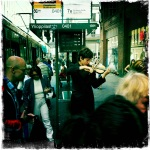 A street performer plays the violin at a tram stop in Helsinki.