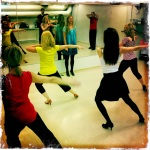 A group of girls practicing for a holiday salsa party practice bachata.